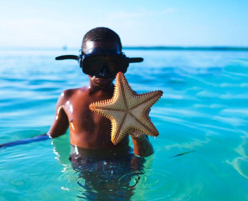 Bambino con stella marina in Oceano Indiano