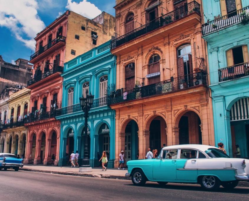 viaggio a Cuba foto auto di fronte a palazzi colorati