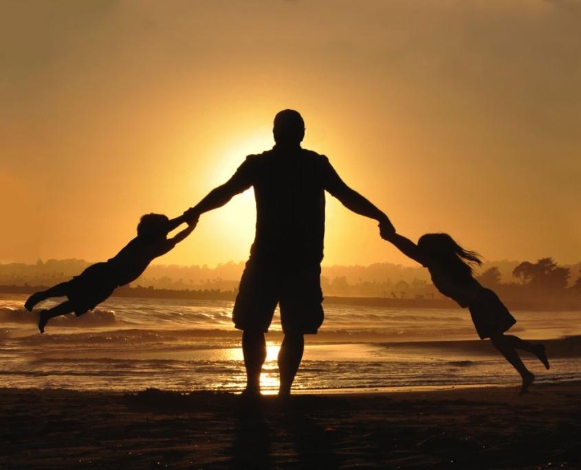 bambini che giocano con padre al tramonto